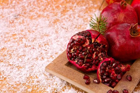 half ball: Juicy pomegranate fruit over wooden vintage table.Fresh ripe pomegranates on wooden background and Christmas decoration.