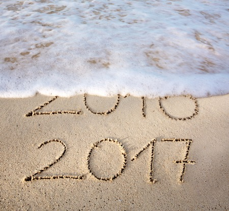 2016 2017 inscription written in the wet beach sand with sea water wave. Inscription 2016 and 2017 on a beach sand, the wave is almost covering the digits 2016. 版權商用圖片