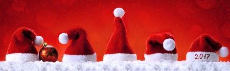 christmastime: Seven red santa hats isolated on red background.Christmas red background with Santa hats.Happy new year 2017 santa hats. Stock Photo