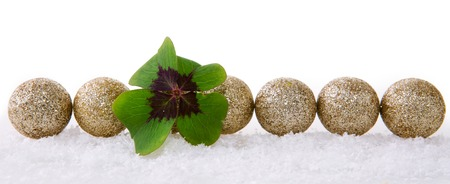 Christmas decoration with snow isolated on white background.Lucky symbols: four-leaf clover and balls . Green cloverleaf and decoration. Stock Photo