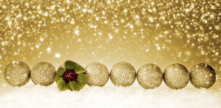 Green clover leaf and christmas balls. Happy symbols: four leaf clover and snow. Golden Christmas background.