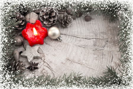 flamme: Christmas decoration with red Advent candle and fir branch frame, top view with copy space on wood. Christmas ornaments border with fir tree branches and snow.