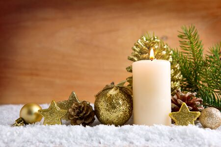 Christmas background with white advent candle and golden decoration.