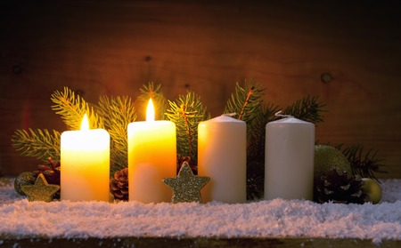 Christmas background with two white advent candles and golden decoration.