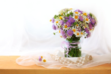 marguerite: Chamomiles bouquett in vase on fabric background. Stock Photo