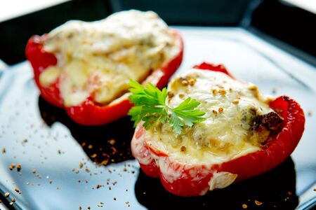 grill: Stuffed Red bell peppers with mushrooms on the black plate.