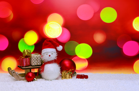 Snowman with Christmas gifts on the sledge isolated on abstract background.