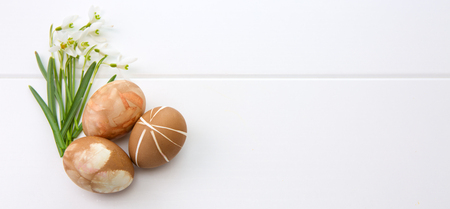 Spring snowdrop isolated on white wooden background. Three brown easter eggs . Stock Photo
