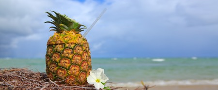 Pina Colada in pineapple in the sand of the beach with the beautiful Caribbean sea in the background.