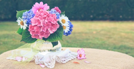 Colorful flowers bouquet in glass vase isolated on green.