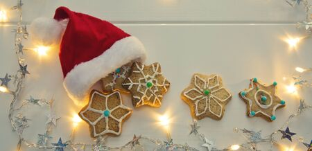 Red Santa Claus hat with Christmas Cookies and garland.