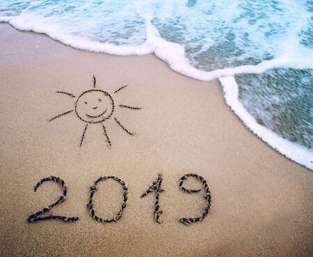 Year 2019 written at the caribbean sand beach with sea wave .