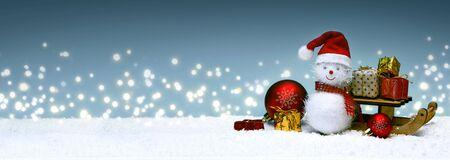 Weihnachtsschneemann mit Geschenken auf dem Schlitten und Schneefall.