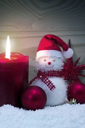 Advent candle and Snowman with red Christmas decoration isolated.