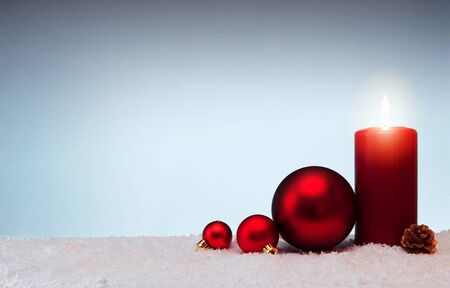Christmas background with Advent candle and red bauble isolated on white snow. Zdjęcie Seryjne