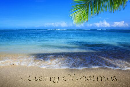 Merry Christmas Inscription written in the white Caribbean sand. Stock Photo