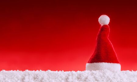 Red Santa Hat and white snow. Christmas background.