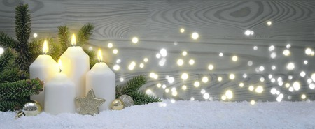Four burning Advent candles with golden decoration and white snow.