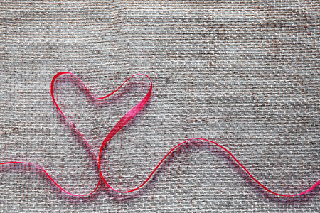 Red heart ribbon isolated on brown cloth background.