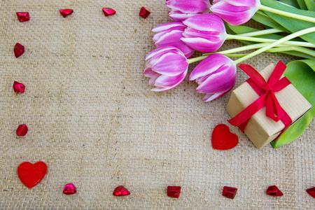郁金香和红色心脏在棕色布料背景。