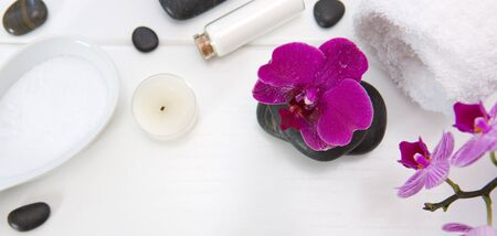 Spa setting with pink orchids, black stones and bath salts on white wood .