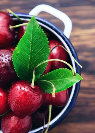 Cherries in the cooking pot on an old wooden background.