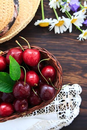 Red Cherries and summer straw hat on brown wooden table.
