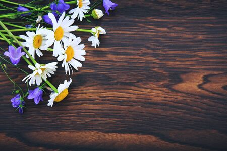 Bouquet of blue flowers and white daisies on brown wood background.