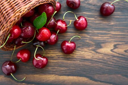 Cherries in the basket pot isolated on old wooden background.