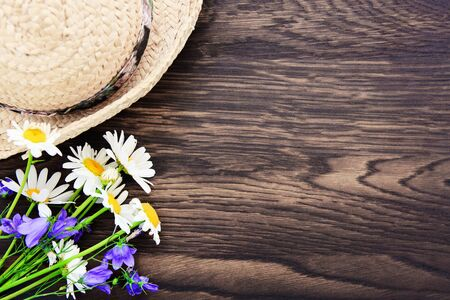 Summer flowers with a straw sun hat on brown wood background.