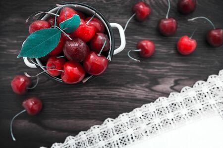 Cherries on brown wooden table with water drops. Banco de Imagens