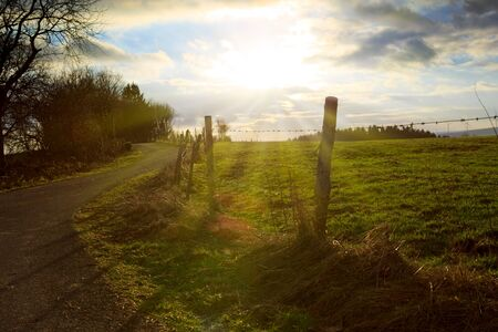 Road in the field in sunny day with clouds in the sky. 版權商用圖片