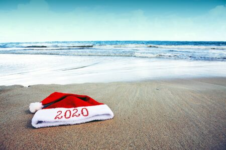 Year 2020 written at the Santa Claus hat on caribbean beach. New Year background