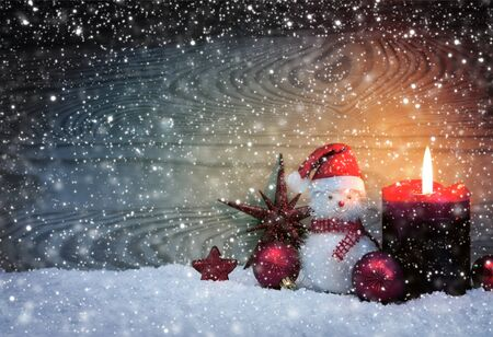 Christmas snowy background with fourth Advent candle and Snowman . Stock fotó