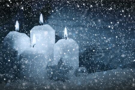 Four burning Advent candles and snowfall. Christmas background.