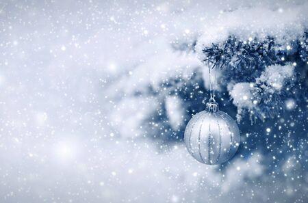 Silberner Weihnachtsball, der an einem Tannenbaum-Zweig hängt. Weihnachten Hintergrund.