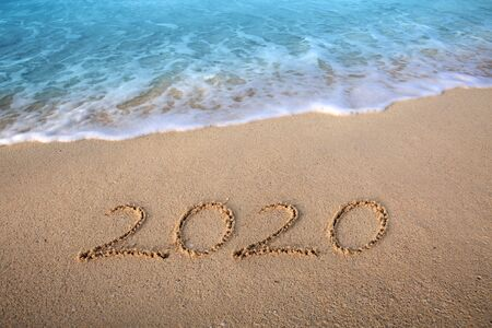 New Year 2020 is coming concept. 2020 inscription written in the wet beach sand with sea water wave
