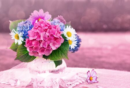 Colorful flowers bouquet in glass vase on tablecloth.