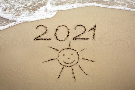Year 2021 written at the caribbean sand beach with Sun drawing