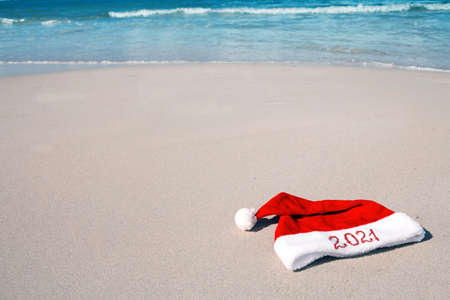 Year 2021 written at the Santa Claus hat on caribbean beach. Stock Photo