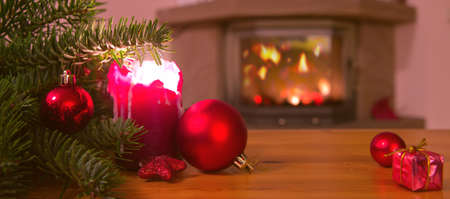 Christmas background with burning candle, fireplace and decorated Christmas tree