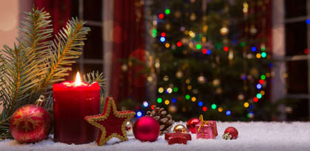 Christmas red candle with decorations and fir tree isolated on lights background. Reklamní fotografie