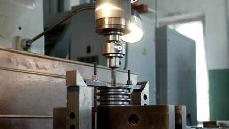 Drilling a hole with a drilling machine in a metal workpiece pulley, close-up, industry, manufacturing pulley