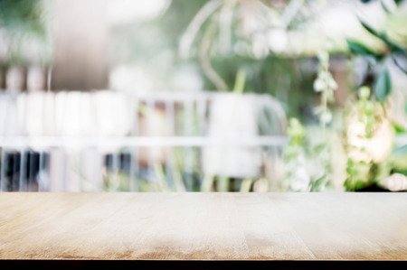 empty wooden table with blurred outdoor garden background.