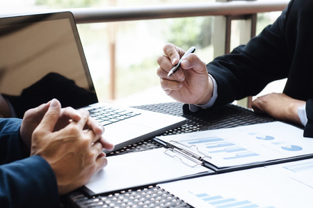 Ejecutivos comerciales reunidos con datos de desempeño de ventas en un lugar de trabajo al aire libre moderno.