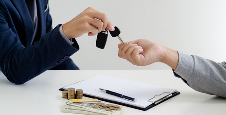 agent giving a car vehicle key to customer, business and transportation. Reklamní fotografie