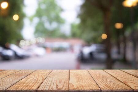 empty wooden desk over blurred coffee shop background