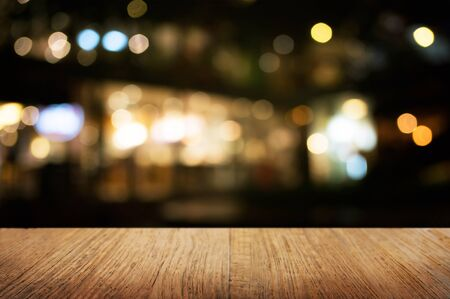 empty wood table in front of blurred montage night market bokeh background Stockfoto