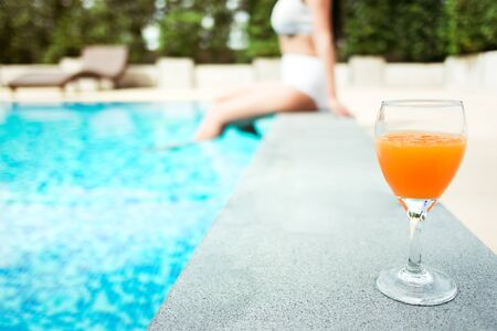 travel and vacation concept - close up of young woman relaxing at a pool in summer with orange juice, selective focus
