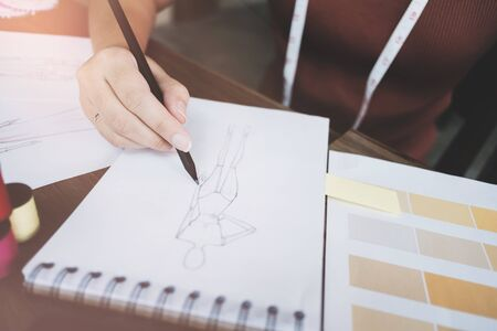 fashion / creative designer working with sketching notebook at modern home studio, selective focus